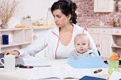 stock photo of telecommuting  - Young Woman With Baby Working From Home - JPG