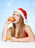 Woman In Santa Claus Hat Eating Mandarins