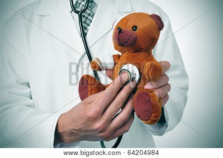 a doctor auscultating a teddy bear with bandages in its head and arm, depicting the pediatric medicine or the veterinary medicine concepts