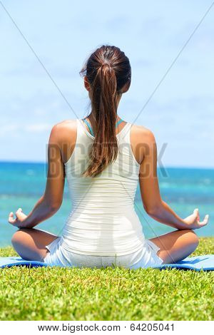 Meditation yoga woman on beach meditating by ocean sea sitting in lotus position with back turned serene and happy. Asian girl sitting relaxing enjoying summer beach.