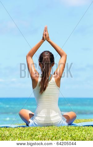 Meditation yoga woman meditating at beach relaxing in yoga pose. Serene relaxed female yoga instructor in calm nature sea scene.