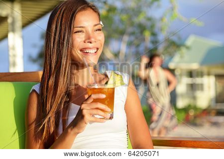 Woman drinking alcohol Mai Tai drink on Hawaii at beach club at sunset. Beautiful girl enjoying alcoholic beverage cocktail outside. Smiling happy mixed race Asian Caucasian woman on Hawaiian beach.