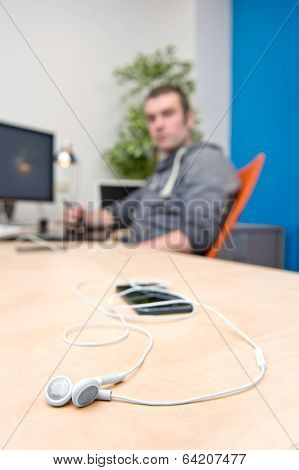 Ear phones, lying on a clean, paperless desk, with a man, working behind a computer in the background. A connectivity concept