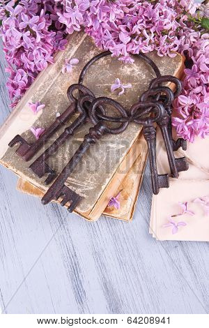 Beautiful composition with old keys and old books on wooden table