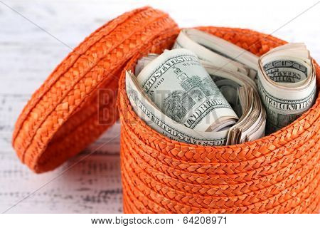 Packs of dollars stored in basket on wooden table