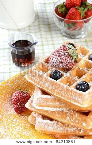 Waffles with strawberries and blueberries covered with powdered sugar. Vertical format with syrup and a bowl of fresh strawberries and a crock.