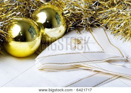 Shiny golden color Christmas New Year decoration ornament balls with textured fabric napkins on a ta