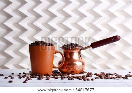 Cup  and cezve full of coffee beans on light background