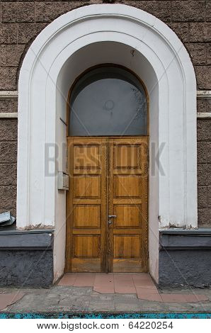 Old Wooden Door In The Wall With A White Arch.