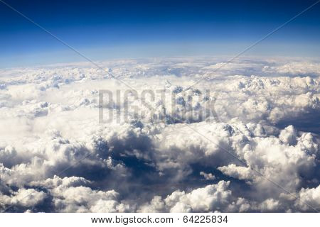 Blue sky and puffy clouds on height of 5000 m