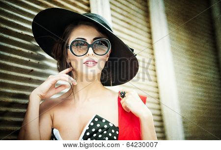 Attractive brunette girl with black hat, red scarf and sunglasses posing outdoor. Beautiful woman