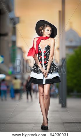 Fashionable lady wearing elegant dress, black hat and red scarf posing outdoor in urban scenery