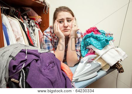 Sad Woman Leaning Against Huge Pile Of Not Ironed Clothes