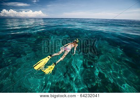 Lady snorkeling in turquoise clear sea