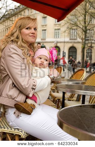 Beautiful Young Mother And Her Baby Daughter In A Parisian Street Cafe