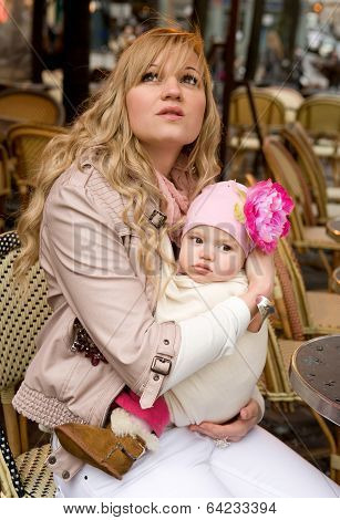 Beautiful Young Mother With Her Baby Daughter In A Parisian Street Cafe