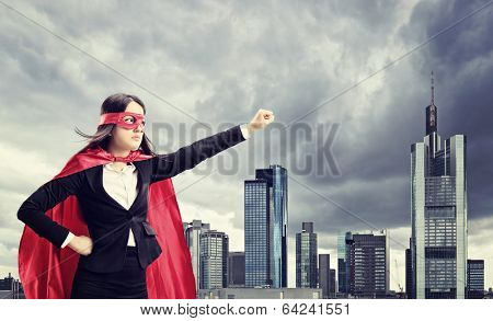 Female superhero standing in front of a dark city
