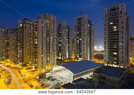 Residential street with new tall buildings at night