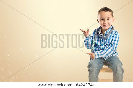 Kid On Chair Pointing Over Ocher Background