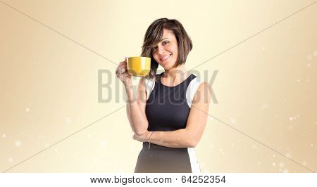 Pretty Girl Holding A Cup Of Coffee Over Ocher Background