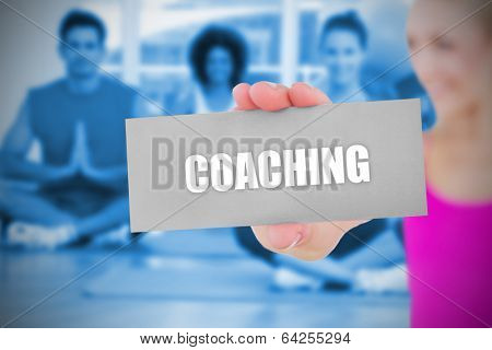 Fit blonde holding card saying coaching against yoga class in gym