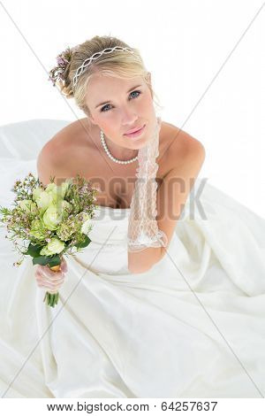 High angle portrait of sensuous bride holding flower bouquet over white background