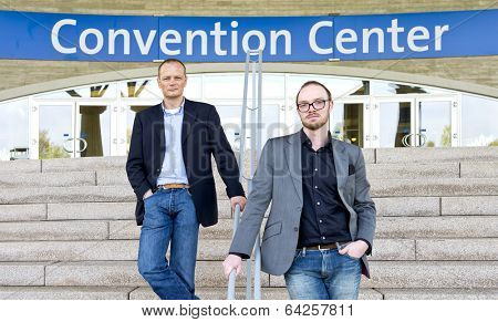 Two smart casual dressed colleagues, posing on the steps in front of a convention center