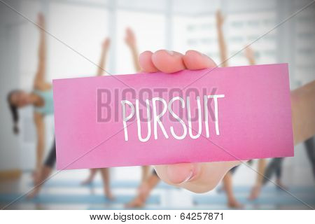 Woman holding pink card saying pursuit against fitness class in gym