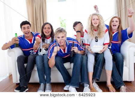 Teenagers Watching A Football Match In The Living-room