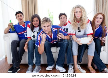 Teenagers Watching A Football Match At Home