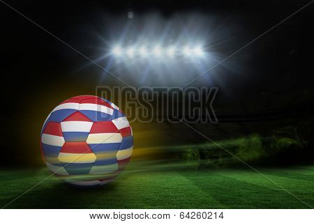 Football in holland colours against football pitch under spotlights