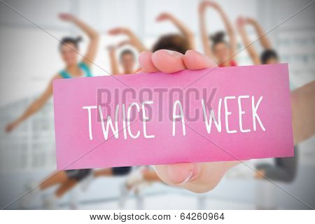 Woman holding pink card saying twice a week against fitness class in gym