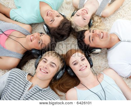 Group Of Friends Listening To Music On The Floor