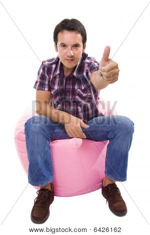 Young Casual Man Seated In A Small Pink Sofa Going Thumbs Up