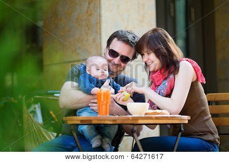Happy Family Of Three Having Breakfast