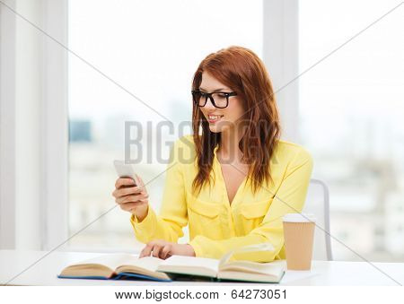 education and technology concept - smiling student girl in eyeglasses with smartphone, books and takeaway coffee at school