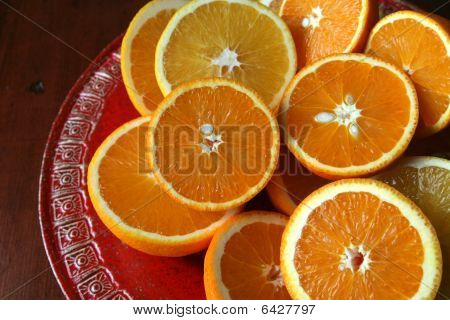 Halved oranges on a red plate