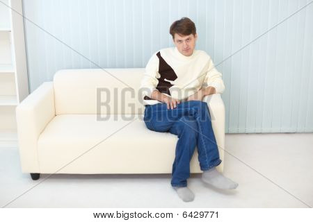 Person In Jeans And Sweater Sits On Sofa