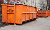 picture of trash truck  - Big metal orange trash containers in the city - JPG