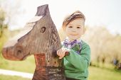 stock photo of baby cowboy  - Cute little boy riding a wooden horse and playing on the playground outdoor - JPG