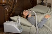 stock photo of cpap machine  - Woman wearing CPAP machine for sleep apnea - JPG