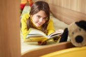 stock photo of girl reading book  - girl lying on bed and reading book - JPG