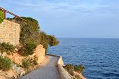 stock photo of costa blanca  - Paved coastal walkway on a summer evening - JPG