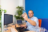 stock photo of self-storage  - A business man taking a selfie in his clean and paperless office - JPG
