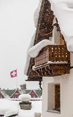 stock photo of chalet  - Swiss chalet during heavy snow with Swiss flag in background - JPG