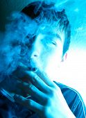stock photo of teen smoking  - Portrait of Smoking Young Man in the Deep Blue light - JPG