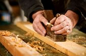picture of joinery  - Skilled carpenter using a handheld plane to smooth and level the surface of a plank of hardwood close up view of his hands the tool and wood shavings