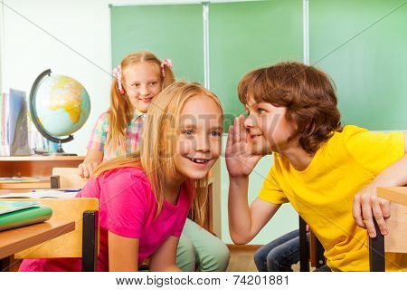 Small boy tells secret to other girl in school