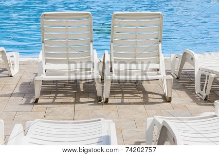 Two lounge chairs by the pool, perfect holiday.