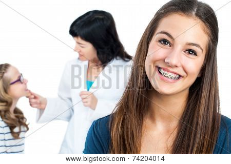 Teen Girl With Braces And Doctor With Patient In Background.